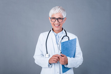 Female mature doctor holding medical records and stethoscope. Healthcare and medical concept. Medicine doctor with stethoscope isolated on background.