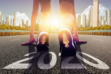 Start of people running on a street road with 2020 symbolises number and sunset light.Goal of Success the winner - Image