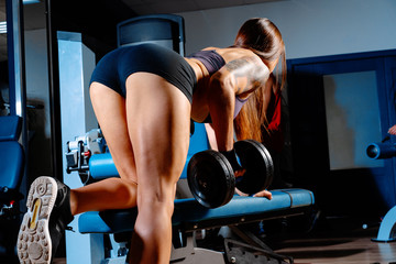 Young woman bodybuilder doing dumbbell pulls in a gym