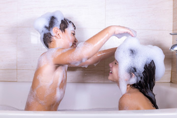 Two kids playing with foam in a bathtub