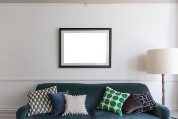 Empty picture frame hanging above a blue sofa in a living room