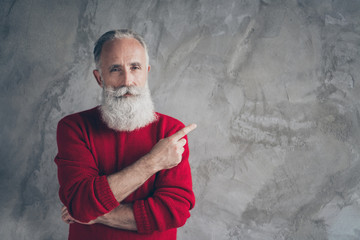 Photo of amazing aged grandpa indicating finger empty space advising new product wear red knitted pullover hipster santa role isolated grey color concrete wall background