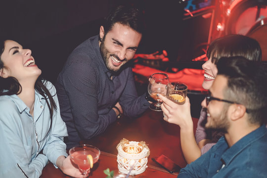 Happy friends having fun in cocktail jazz bar - Young millennial people drinking ad laughing together in nightclub - Nightlife entertainment and youth culture lifestyle holidays concept