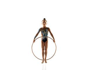 Little flexible girl isolated on white studio background. Little female model as a rhythmic...