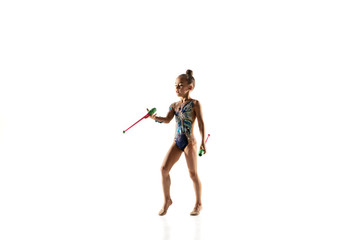 Little flexible girl isolated on white studio background. Little female model as a rhythmic gymnastics artist in bright leotard. Grace in motion, action and sport. Doing exercises with the maces.