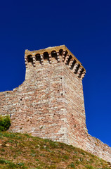 Assisi ancient medieval walls ruins at the top of the town with blue sky above