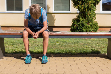 Unhappy sad boy sitting in closed position with his head down. School bullying, learning...