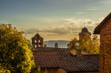 Perugia roofs at sunset with old belfry , autumn leaves and beautiful sky