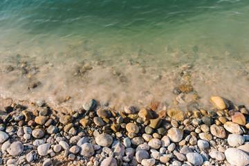 Steine am Ufer mit türkisfarbenen Wasser