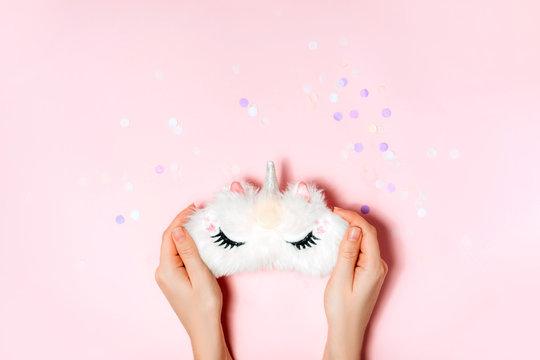Unicorn sleep mask in girls hand.