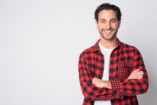 Portrait of happy Hispanic hipster man smiling with arms crossed