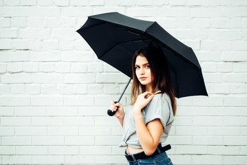 20 year old girl stands under a black umbrella against a white wall