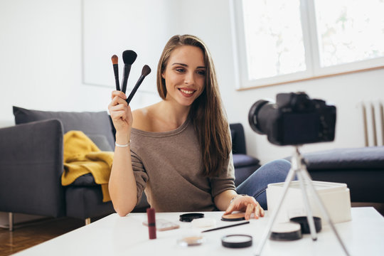 Young adult woman vlogging about cosmetics, skin care products