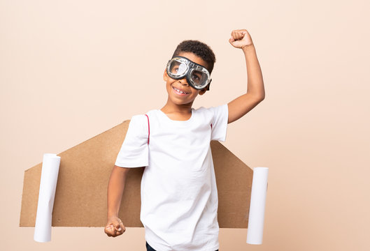 African American boy  with aviator hat and with wings over isolated background