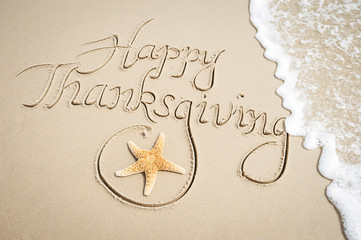 Happy Thanksgiving message handwritten on smooth sand beach with decorative starfish and oncoming wave