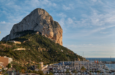 Huge limestone rock located in Natural Park of Penyal d'Ifac situated in Calpe touristic town. Moored yachts boats in the harbour of the city, Costa Blanca, Province of Alicante, Spain