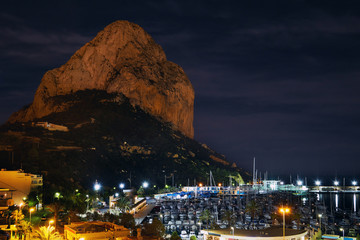 Calpe nightview. Natural Park of Penyal d'Ifac massive limestone rock in the Mediterranean Sea, illuminated streets near harbour moored yachts at marina. Province of Alicante, Costa Blanca, Spain