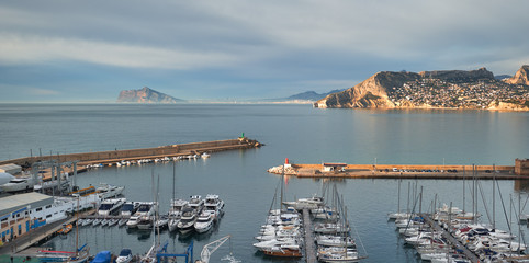 Picturesque scenery view to the calm Mediterranean Sea moored yachts in a row at harbour of Calpe, Costa Blanca, Spain
