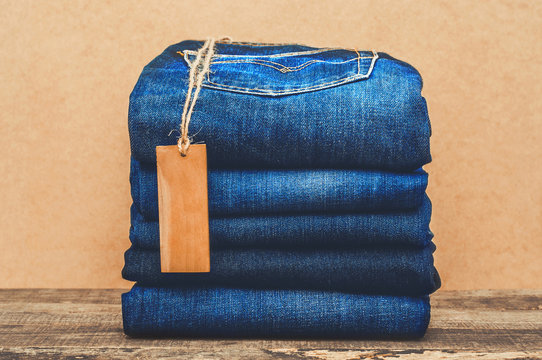 Collection of blue jeans with a label on the wooden table for as a background or advertisement a denim clothing