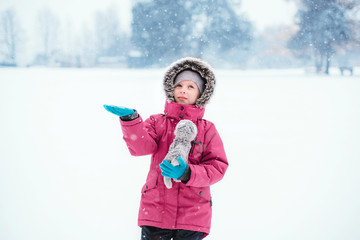 Cute adorable funny Caucasian smiling girl child in warm clothes red pink jacket playing with snow catching snowflakes during cold winter snowy day. Kids outdoor seasonal activity.