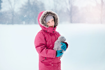 Cute adorable Caucasian smiling girl child in warm clothes red pink jacket playing looking at  falling snow snowflakes during cold winter snowy day. Kids outdoor seasonal activity.