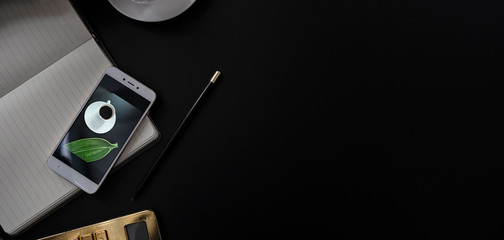 Dark modern desktop with office accessories, smartphone, pencil, notebook and gold calculator on a black background with copy space. Panoramic banner.