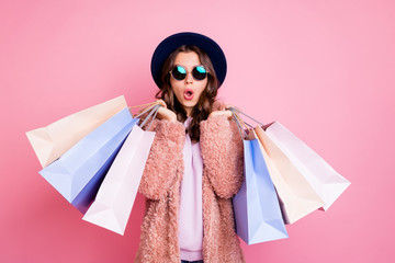 Photo of pretty millennial lady carry many packs shopper tourism abroad look unbelievable sales low prices mall wear fluffy jacket sun specs blue hat isolated pink background Fototapete