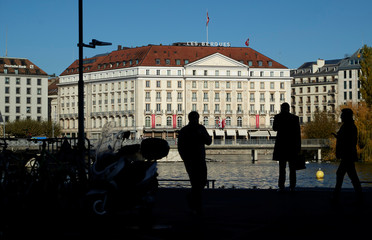 People are silhouetted in front of the Four Season Les Bergues hotel in Geneva