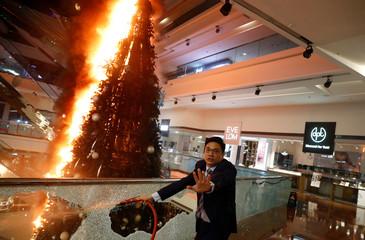 A man reacts as he tries to extinguish a burning Christmas tree at Festival Walk mall in Kowloon Tong, Hong Kong