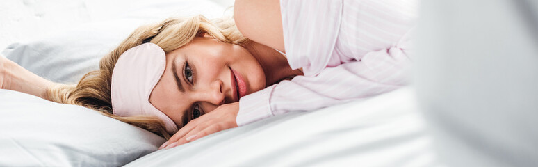 panoramic shot of cheerful woman with eye mask lying on bed at home