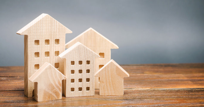 Miniature wooden houses. Real estate. City. Agglomeration and urbanization. Market Analytics. Demand for housing. Rising and falling home prices. Population