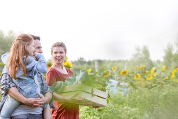 Portrait of a family of famers carrying their vegetables home in wooden boxes, the Father is carrying their daughter