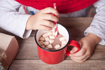 Foto auf Acrylglas Schokolade Child's hand holding red mug of Christmas cocoa on the wooden table