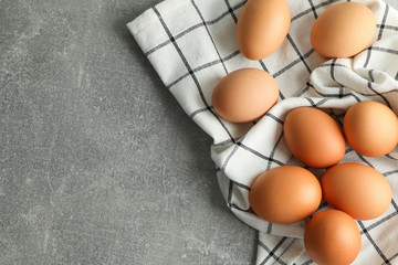 Chicken eggs in kitchen towel on gray background, space for text