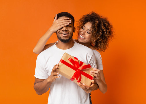 Beautiful girl covering her boyfriend eyes with present