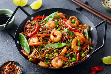 Stir fry noodles with vegetables and shrimps in black iron pan. Dark background. Close up.