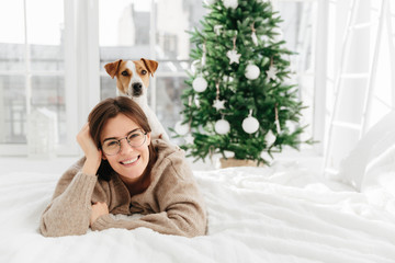 Pretty cheerful woman wears big optical round glasses, lies on bed, her dog poses on back, have fun together, spend winter holidays at home, decorated green Christmas tree. Coziness, winter, festivity Wall mural