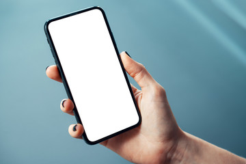 Mockup image of woman's hand holding thin bezels mobile phone with blank screen in glossy corporate environment - Image