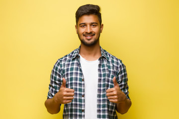 Young indian male looking like a tourist, turn up his fingers isolated on yellow background.