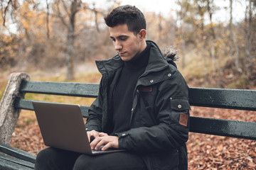 Young Man in autumn Park. Freelance man working on his laptop sitting on a bench in the park. Student preparing for the exams outdoors by using a laptop .