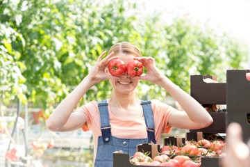 Young farmer playing with tomatoes in Greenhouse