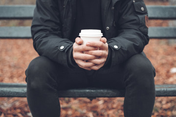 Young man sitted in a bench holding disposable coffee cup in the park in autumn season .
