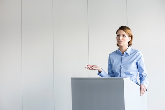 Young business speaker standing in conference room