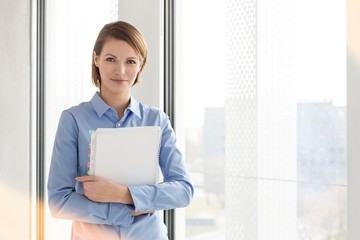 Young businesswoman standing while holding document in office