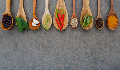 Various of spices and herbs in wooden spoons. Flat lay spices ingredients chili ,peppercorn, rosemary, thyme on dark stone background.