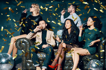 Diverse group of friends having fun enjoying party and drinking champagne