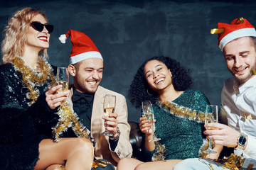Group of happy smiling friends celebrate New Year together, having fun and drinking champagne