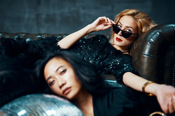 Two pretty multiethnic young women relaxed after party