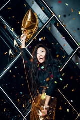 Pretty happy asian woman having fun and dancing at party holding golden balloon