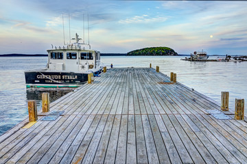 Bar Harbor, USA - June 8, 2017: View of dock in downtown village in summer during sunset twilight with full moon rising
